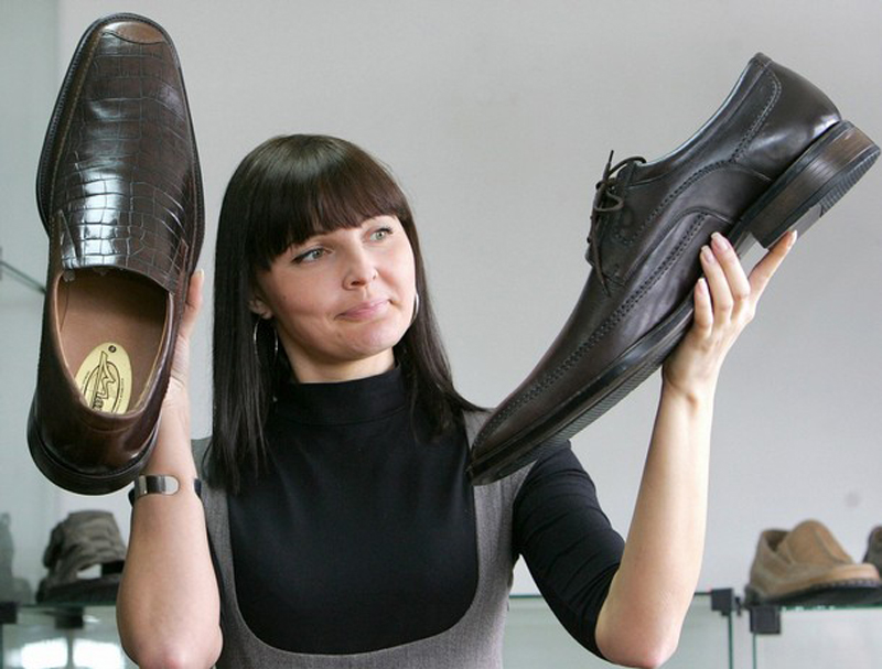 Девушка держит в руках большие мужские туфли